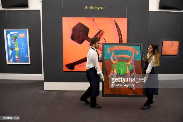 Gallery assistants walk past Andy Warhol Hammer and Sickle 1976 with David Hockney Gauguin's Chair 1988 at the London press view of Impressionist...