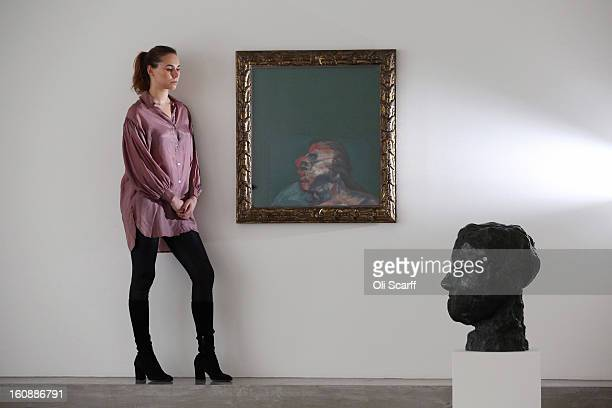 A gallery employee admires a painting by British artist Francis Bacon entitled 'Miss Muriel Belcher' and a sculpture by French artist Auguste Rodin...