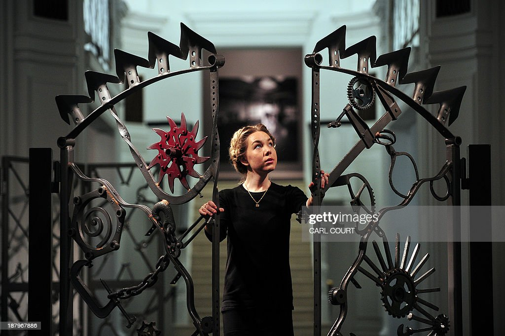 A gallery employee poses for pictures next to an iron gate artwork (called 'Untitled VI') designed by US musician Bob Dylan, during a photocall for an exhibition entitled 'Bob Dylan: Mood Swings' at the Halcyon Gallery in central London, on November 14, 2013. The exhibition, which runs until January 25, 2014, features Dylan's artworks and includes iron sculptures, paintings and bullet-ridden car doors. AFP PHOTO/CARL COURT