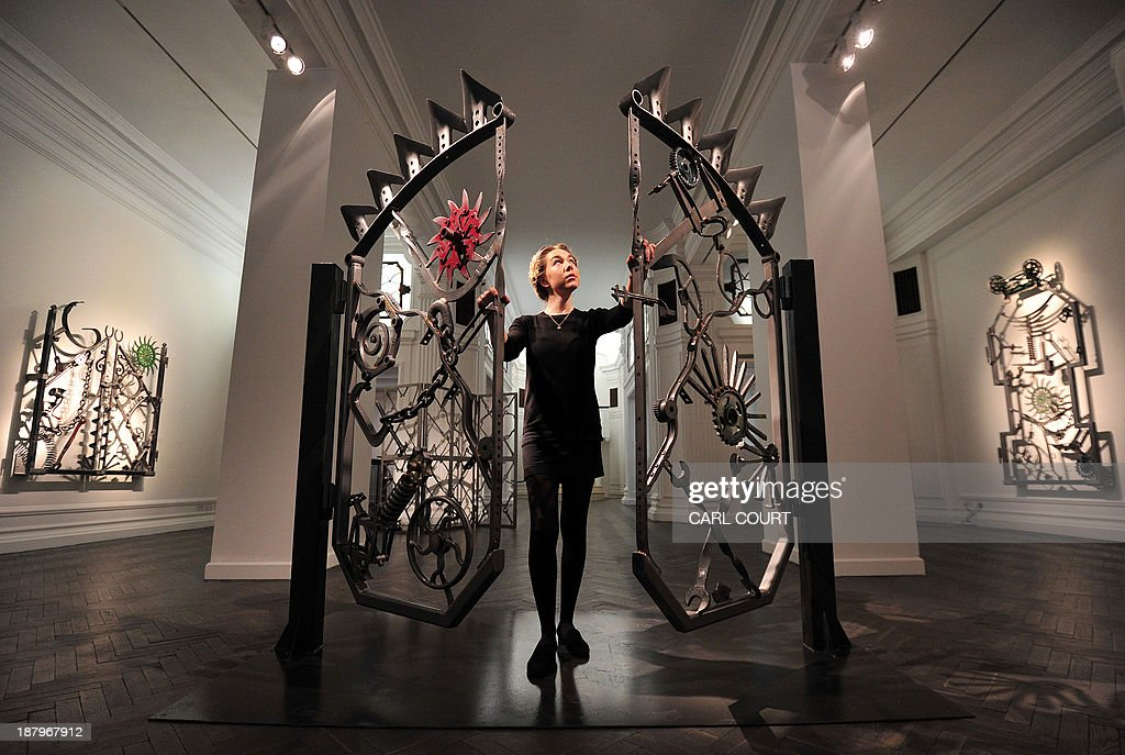 A gallery employee poses for pictures next to an iron gate artwork (called 'Untitled VI') designed by US musician Bob Dylan during a photocall for an exhibition entitled 'Bob Dylan: Mood Swings' at the Halcyon Gallery in central London, on November 14, 2013. The exhibition, which runs until January 25, 2014, features Dylan's artworks and includes iron sculptures, paintings and bullet-ridden car doors.
