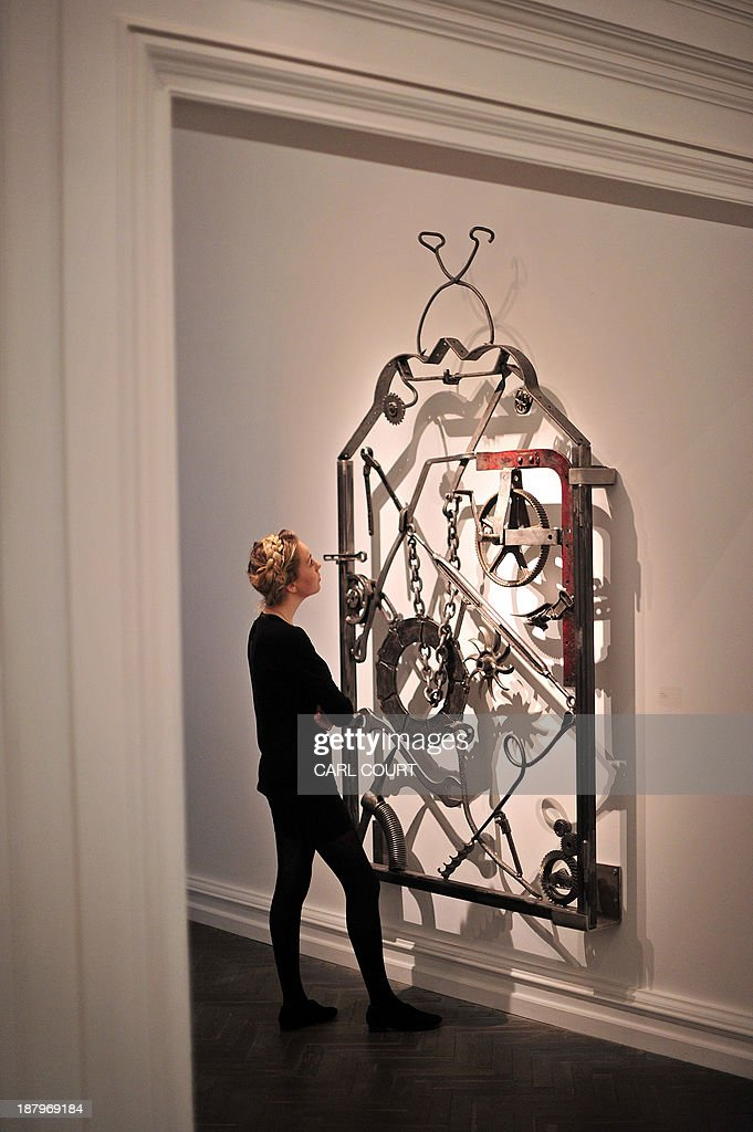 A gallery employee poses for pictures next to an iron gate artwork (called 'Untitled IV') designed by US musician Bob Dylan, during a photocall for an exhibition entitled 'Bob Dylan: Mood Swings' at the Halcyon Gallery in central London, on November 14, 2013. The exhibition, which runs until January 25, 2014, features Dylan's artworks and includes iron sculptures, paintings and bullet-ridden car doors. AFP PHOTO/CARL COURT