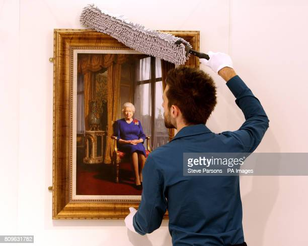 Gallery Manager Alex Prior hangs a portrait of HM Queen Elizabeth II which is being displayed at the EXPO Fine Art gallery in the Departures area of...