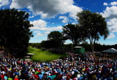 A gallery of fans watch as Jason Dufner of the United States putts on the 13th green during the final round of the 95th PGA Championship at Oak Hill...