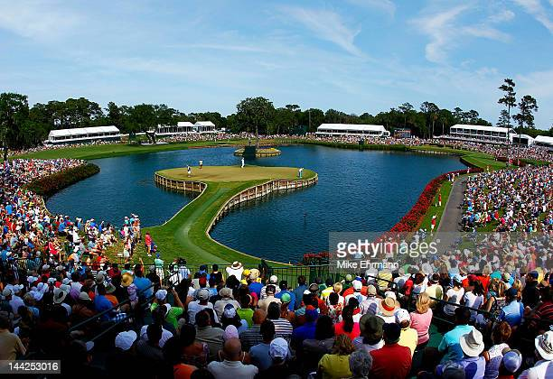 A gallery of fans watch as Rickie Fowler of the United States putts on the 17th green during the third round of THE PLAYERS Championship held at THE...