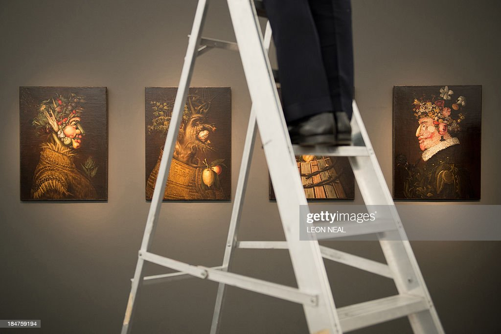 A gallery owner adjusts a light as artworks entitled 'The Four Seasons' by Italian artist Giuseppe Arcimboldo are displayed at the Frieze Masters Art Fair in north London, on October 16, 2013. Running from October 17-20, 2013, the Frieze Masters exhibition aims to give a unique view of the relationship between old and new art. AFP PHOTO / LEON NEAL CAPTION