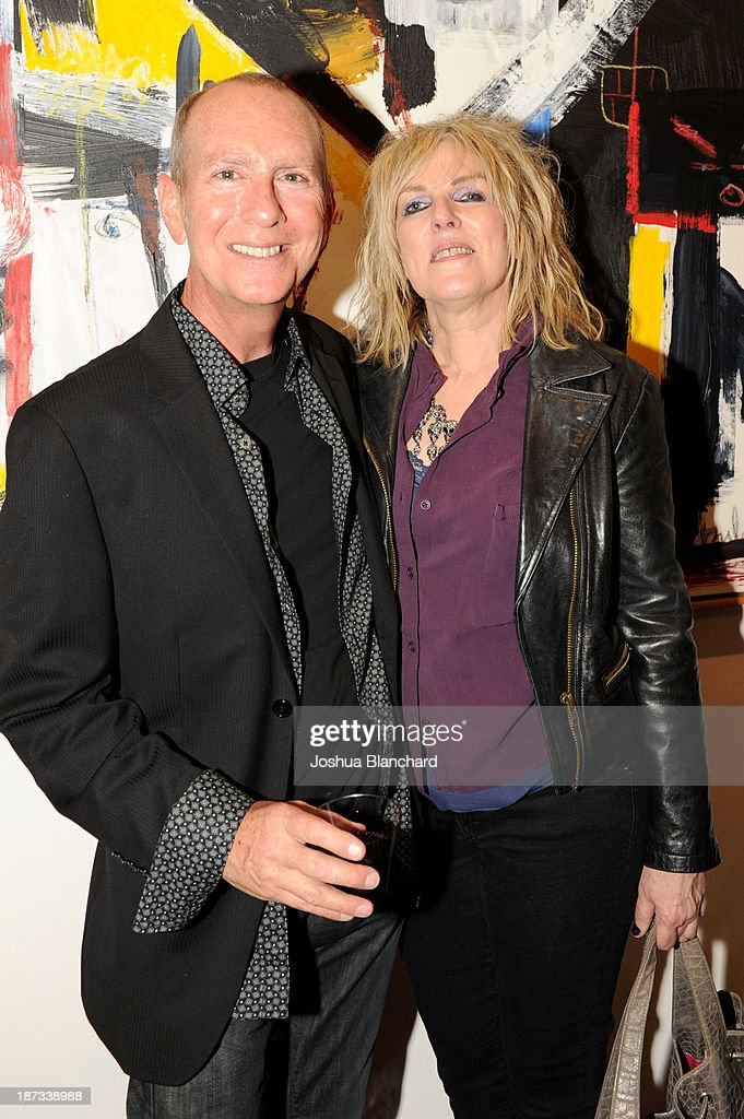 Gallery Owner Sam Milgrom (L) and singer/songwriter Lucinda Williams arrive at Mr. Musichead Gallery for the 'Miles Davis: The Collected Artwork' Launch Party on November 7, 2013 in Los Angeles, California.