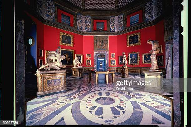 Gallery room in the Uffizi Museum w red walls mosaic marble floor shell cupola ceiling filled w paintings various sculptures