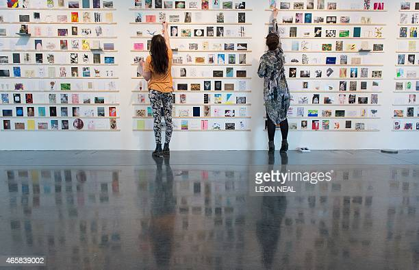 Gallery team members apply numbered stickers as they make final adjustments to the displays at the 'RCA Secret' postcard art sale at the Royal...