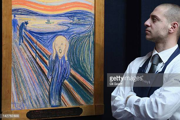 A gallery technician at Sotheby's auction house stands guard in front of 'The Scream' by Edvard Munch on April 12 2012 in London England The iconic...