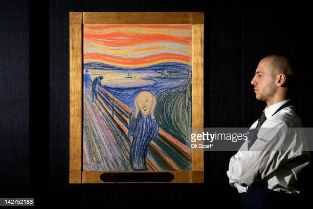 A gallery technician at Sotheby's auction house views 'The Scream' by Edvard Munch on April 12 2012 in London England The iconic painting is on...