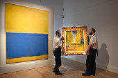 Gallery technicians carry Vincent Van Gogh's 'L'Allee des Alyscamps' painted in 1888 past Mark Rothko's 'Untitled as the works go on show for the...
