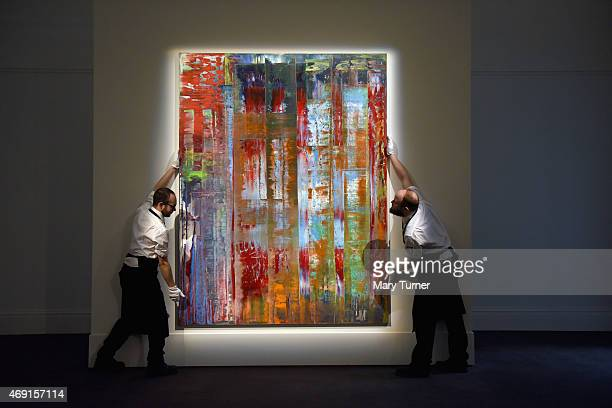 Gallery technicians lift Gerhard Richter's 'Abstraktes Bild' into place as the work goes on show at Sotheby's on April 10 2015 in London England The...