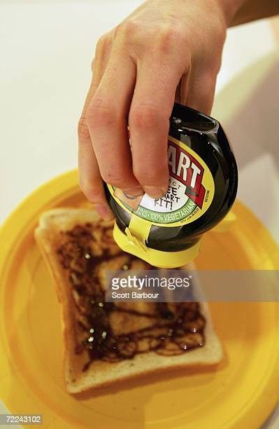Gallery visitor squeezes a tube of Marmite onto a piece of toast during the Marmart exhibition at the Air Gallery on October 23 2006 in London...