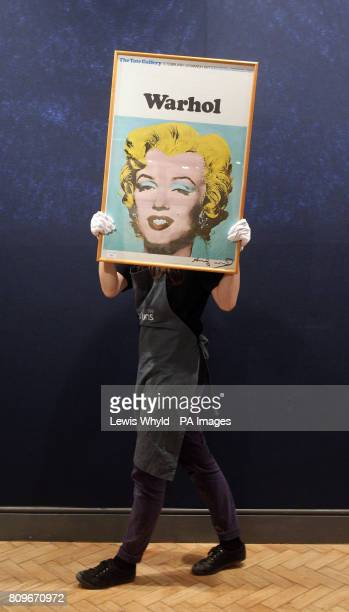 A gallery worker carries a signed print entitled Marilyn Monroe by Andy Warhol estimated to fetch pound1500 at Bonhams in their print auction in...