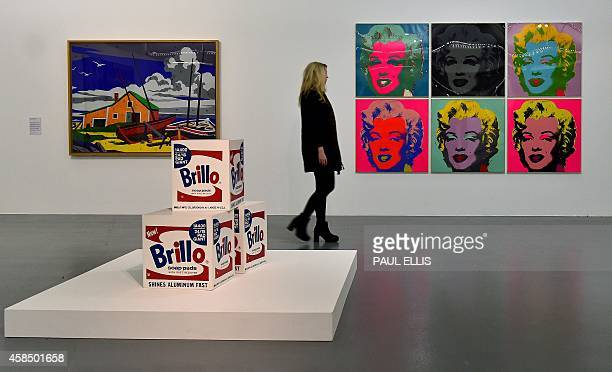 A gallery worker poses for pictures as she looks at Andy Warhol's Untitled artwork of Marilyn Monroe at the Tate Liverpool in northwest England on...