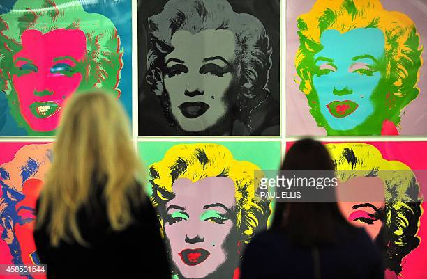 Gallery workers pose for pictures as they look at Andy Warhol's Untitled artwork of Marilyn Monroe at the Tate Liverpool in northwest England on...