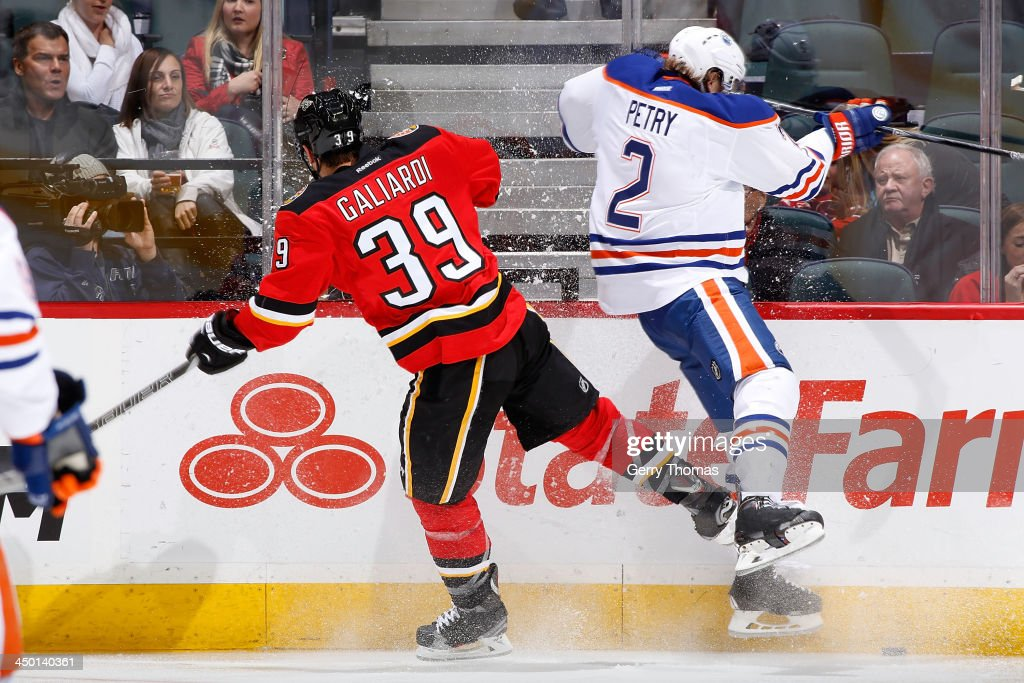 TJ Galliardi #39 of the Calgary Flames collides wth <a gi-track='captionPersonalityLinkClicked' href=/galleries/search?phrase=Jeff+Petry&family=editorial&specificpeople=570439 ng-click='$event.stopPropagation()'>Jeff Petry</a> #2 of the Edmonton Oilers at Scotiabank Saddledome on November 16, 2013 in Calgary, Alberta, Canada.