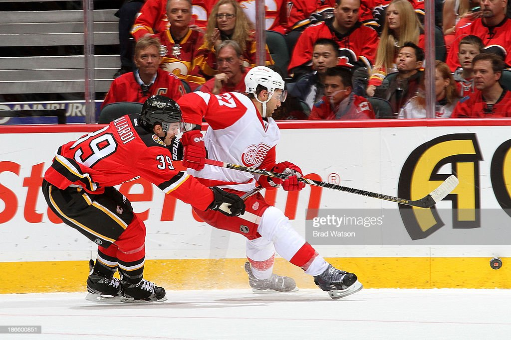 TJ Galliardi #39 of the Calgary Flames skates against Kyle Quincey #27 of the Detroit Red Wings at Scotiabank Saddledome on November 1, 2013 in Calgary, Alberta, Canada.
