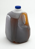 A sealed gallon plastic container of tea.