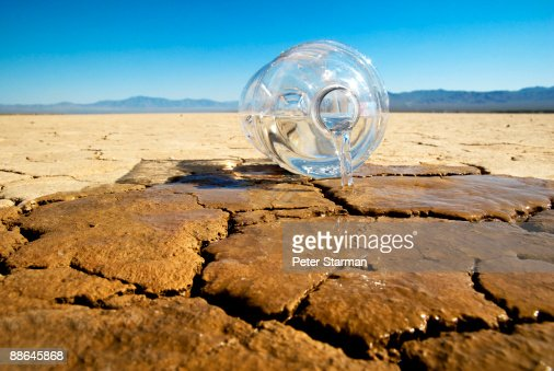 Gallon of water spilling onto dry lake bed.