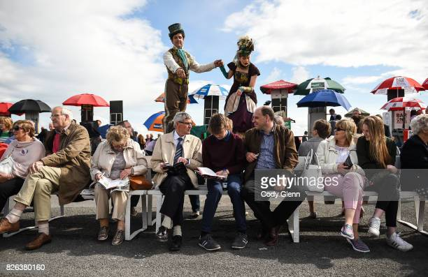 Galway Ireland 4 August 2017 Les Pompadou stilt walkers Aiden Phelan and Beau Holland look for tips from racegoers ahead of the first race during the...