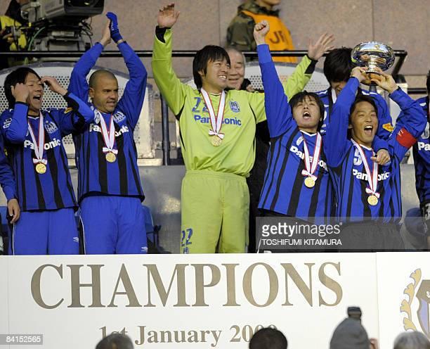 Gamba Osaka captain Satoshi Yamaguchi raises the Emperor's Cup high with teammates Masato Yamazaki Roni goalkeeper Yosuke Fujigaya and Yasuhito Endo...