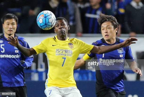 Gamba Osaka defender Daiki Niwa and midfielder Yasuhito Endo fight for the ball with Jiangsu Suning midfielder Ramires Santos during the AFC...