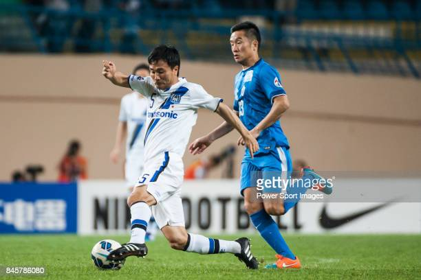 Gamba Osaka defender Konno Yasuyuki fights for the ball with Guangzhou RF midfielder Li Yan during the 2015 AFC Champions League Group Stage F match...