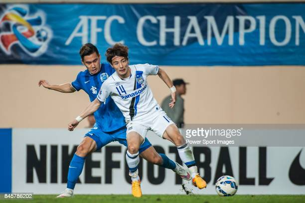Gamba Osaka defender Yonekura Koki fights for the ball with Guangzhou RF defender Jin Yangyang during the 2015 AFC Champions League Group Stage F...