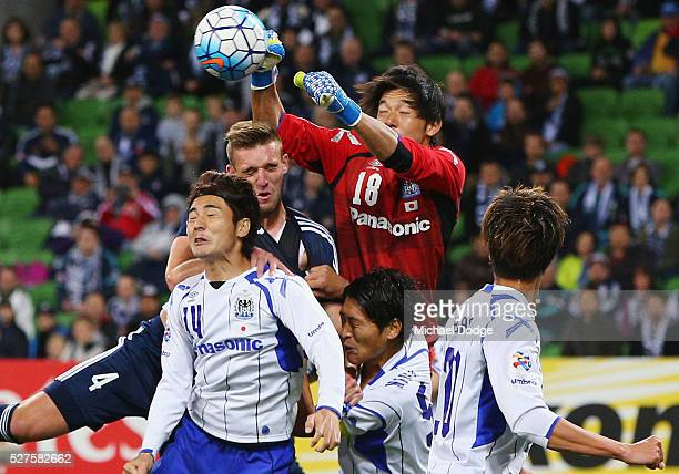 Gamba Osaka Goalkeeper Yosuke Fujigaya defends the ball away from Nick Ansell of the Victory during the AFC Champions League match between Melbourne...
