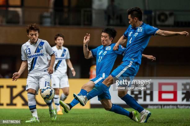 Gamba Osaka midfielder Abe Hiroyuki fights for the ball with Guangzhou RF defender Jiang Zhipeng and Guangzhou RF defender Jin Yangyang during the...