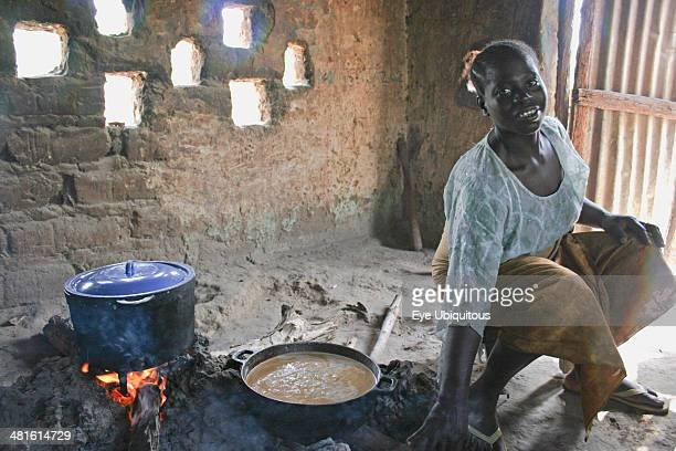 Gambia Western Gambia Tanji Young woman cooking a traditional Gambian dish of groundnut sauce called mafay over open fire in kitchen situated outside...