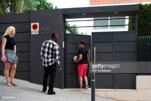 A Gambian Barcelona's supporter returns a ball to a friend of Barcelona's Brazilian forward Neymar after coming out from Neymar's house in Barcelona...