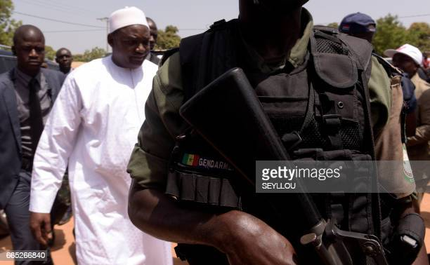 Gambian President Adama Barrow arrives at a polling station flanked by an armed gendarme in Bakau on April 6 2017 during legislative elections...