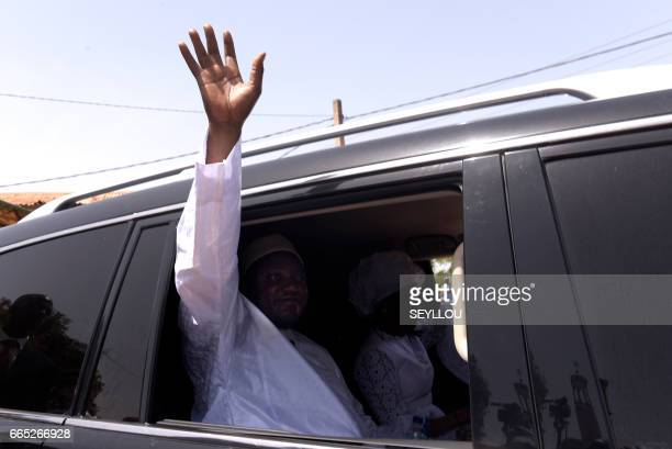 Gambian President Adama Barrow waves from a car as he leaves a polling station in Bakau on April 6 2017 during legislative elections Gambians head to...