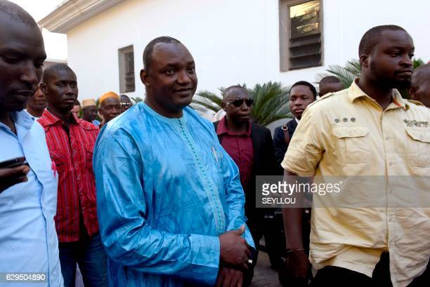 Gambian presidentelect Adama Barrow flanked by his supporters arrives at a hotel in Banjul for a meeting with four African heads of state on December...