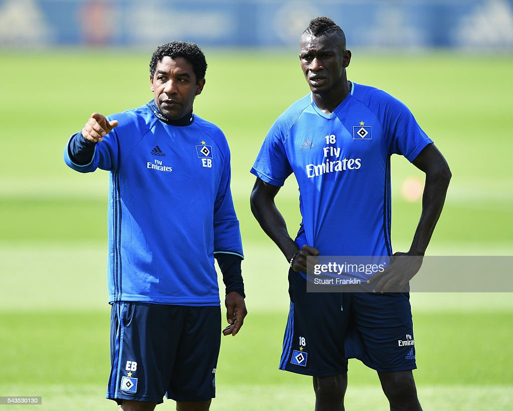 Gambian refugee Bakery Jatta talks with a member of staff during the first training session of Hamburger SV after the summer break on June 29, 2016 in Hamburg, Germany.