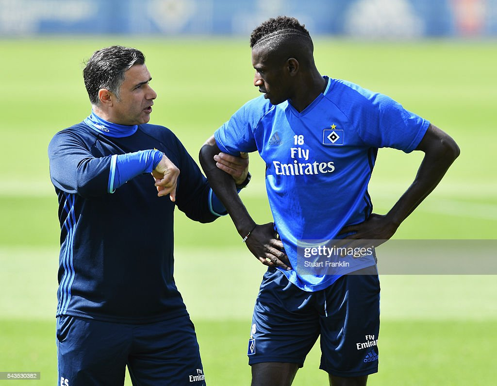 Gambian refugee Bakery Jatta talks with Erdinc Sözer, assistant coach of Hamburger SV during the first training session of Hamburger SV after the summer break on June 29, 2016 in Hamburg, Germany.