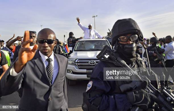 TOPSHOT Gambia's new president Adama Barrow waves as he leaves Banjul airport on January 26 2017 in Banjul after returning from Senegal Jubilant...