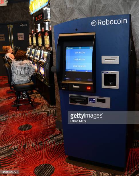 Gamblers play slot machines near a newlyinstalled Robocoin ATM that accepts Bitcoin at the D Las Vegas on May 24 2014 in Las Vegas Nevada The machine...