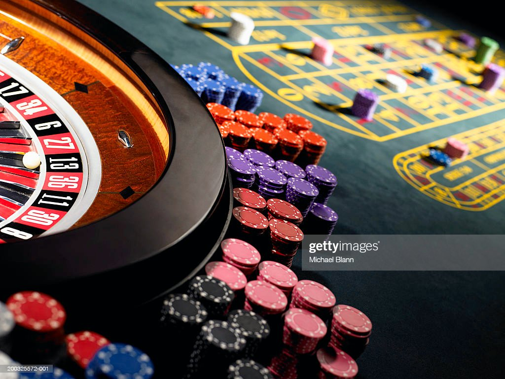 Gambling chips stacked around roulette wheel on gaming table : Stock Photo