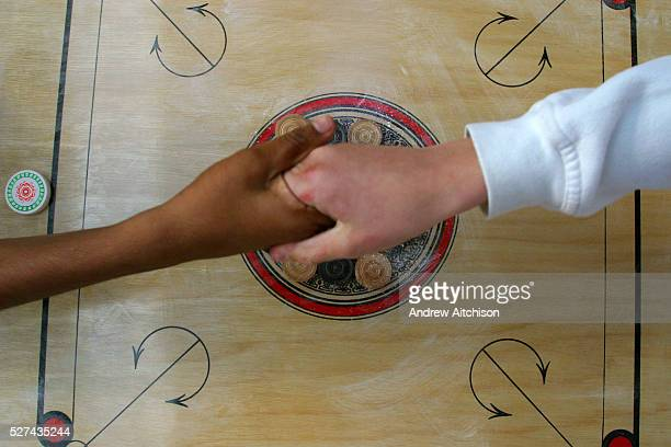 A game of Carrom between 2 contestants begins with a handshake The Carrom Caf International competition 2003 was held at Spitalfield's market London...