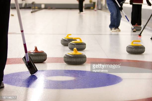 A game of curling on an ice rink with people holding brooms