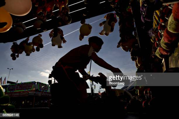 A game operator arranges prizes in the Balloon Burst game during the Dreamland Amusements carnival in the parking lot of the Marley Station Mall in...