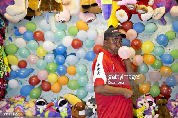 A game operator blows up a balloon at his booth during the Dreamland Amusements carnival in the parking lot of the Marley Station Mall in Glen Burnie...