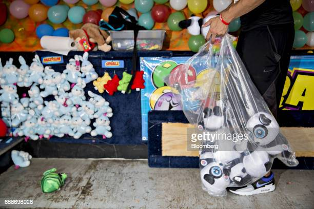 A game operator prepares his booth during the Dreamland Amusements carnival in the parking lot of the Marley Station Mall in Glen Burnie Maryland US...