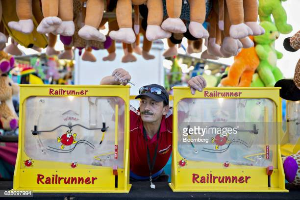 A game operator waits for customers at a booth in the parking lot of the Marley Station Mall during the Dreamland Amusements carnival in Glen Burnie...