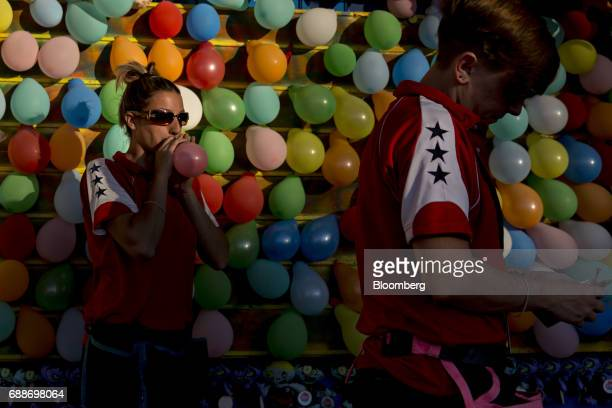 Game operators work in the Balloon Burst booth during the Dreamland Amusements carnival in the parking lot of the Marley Station Mall in Glen Burnie...