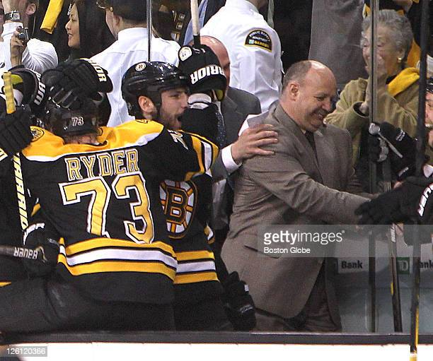 Game Seven of the Eastern Conference Finals Bruins Coach Claude Julien is congratulated by players including Milan Lucic on the bench at the end of...