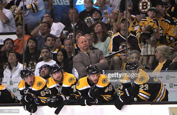 Game Seven of the Eastern Conference Finals Bruins players look along with coach Claude Julien at action in front of the Tampa net with seconds left...